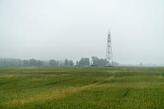 Torre dell'orologio nel campo nebbioso fotografia stock