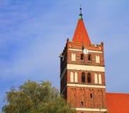 Torre della chiesa luterana di Friedland con un orologio nello stile gotico Fotografia Stock