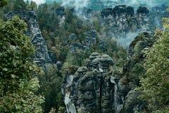 Torre della roccia dell'arenaria nella valle profonda di autunno del Bohemian Svizzera del parco nazionale Paesaggio nebbioso con immagine stock libera da diritti