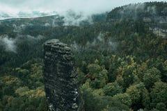 Torre della roccia dell'arenaria nella valle profonda di autunno del Bohemian Svizzera del parco nazionale Paesaggio nebbioso con fotografia stock