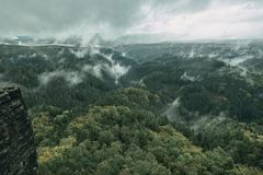 Torre della roccia dell'arenaria nella valle profonda di autunno del Bohemian Svizzera del parco nazionale Paesaggio nebbioso con fotografie stock