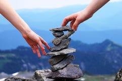 Torre della roccia equilibrata mano, fondo della montagna, concetto di lavoro di squadra Fotografie Stock Libere da Diritti