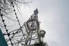 Torre della TV con i trasmettitori di telefono contro un cielo nuvoloso fotografie stock