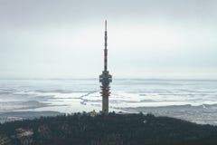 Torre della TV sopra il paesaggio nevoso Immagine Stock