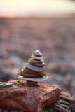 Torre delle pietre nella forma dell'albero di natale decorata con vetro verde sul fondo della spiaggia Immagini Stock Libere da Diritti