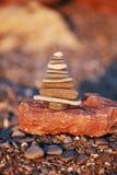 Torre delle pietre nella forma dell'albero di natale sul fondo della spiaggia Fotografia Stock Libera da Diritti