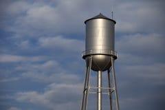 Torre di acqua d'argento alta davanti ad un cielo blu nuvoloso fotografie stock libere da diritti