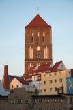 Torre di alta chiesa veduta dietro le case Immagini Stock