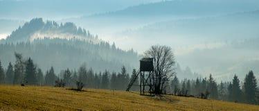 Torre di caccia che sta nelle montagne vicino alla foresta su un passo Fotografia Stock