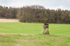 Torre di caccia su un campo vicino ai cervi di caccia della foresta Giorno nuvoloso Fotografie Stock