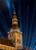Torre di chiesa con gli orologi - proiettore blu nel cielo Immagini Stock Libere da Diritti