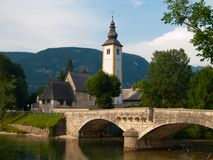 Torre di chiesa e ponte della pietra nel lago Bohinj Fotografia Stock
