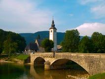 Torre di chiesa e ponte della pietra nel lago Bohinj Immagini Stock