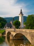 Torre di chiesa e ponte della pietra nel lago Bohinj Immagine Stock