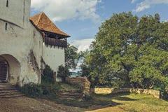 Torre di chiesa e portone fortificati dell'entrata Immagini Stock