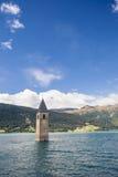 Torre di chiesa incavata in lago nelle alpi Fotografia Stock