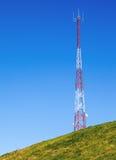 Torre di comunicazione alta su una collina con cielo blu Fotografie Stock