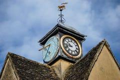 Torre di orologio e banderuola sopra costruzione in Inghilterra fotografie stock