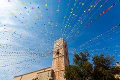 Torre di orologio e bandiere di festa in una cittadina Immagini Stock