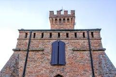 Torre di orologio merlata del muro di mattoni con la finestra porpora Fotografia Stock