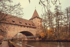 Torre di pietra e piccolo ponte attraverso il fiume ed il parco nella città storica fotografia stock