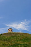 Torre di pietra sola su una collina verde Fotografia Stock