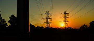 Torre di potere ad alta tensione al tramonto Fotografie Stock Libere da Diritti