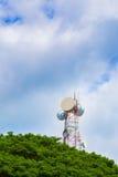 Torre di telecomunicazione con gli alberi verdi ed il cielo blu nuvoloso Fotografie Stock