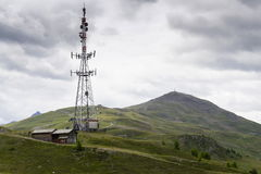 Torre di telecomunicazione con Monte della Neve nel fondo Fotografia Stock Libera da Diritti