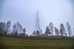 Torre di telecomunicazione nella nebbia fotografia stock