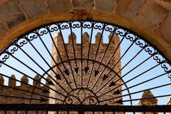 Torre di un castello dietro un portone elegante del ferro Immagine Stock