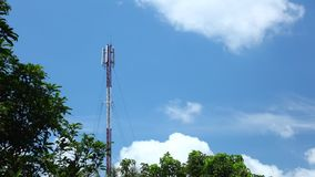 Torre dos coms da rede do telefone celular com cloudscape e copas de árvore video estoque
