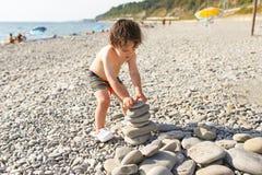Torre dos seixos da construção da criança na praia Fotografia de Stock Royalty Free