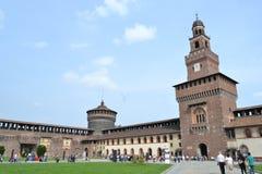 Torre e fortificazioni medievali di Milan Sforza Castle con il giardino interno, il prato dei papaveri e la parete antica del mat fotografia stock