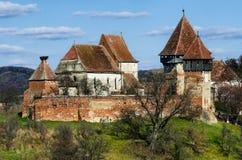 Torre e paredes da igreja fortificada Alma Vii, a Transilvânia. Roma Imagens de Stock