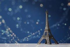 A torre Eiffel da lembrança em um fundo azul com bokeh colorido ilumina-se Foto de Stock Royalty Free