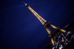 Torre Eiffel em Paris na noite com o farol Imagem de Stock Royalty Free