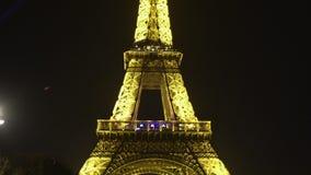 A torre Eiffel iluminada brilhante contra o fundo escuro do céu noturno em Paris, zumbe dentro filme