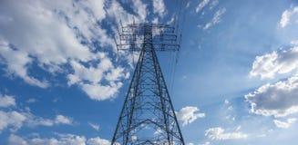 Torre eléctrica centrada sobre el cielo azul y las nubes Imagenes de archivo