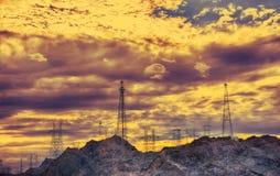 Torre eléctrica de alto voltaje en la puesta del sol Fotografía de archivo libre de regalías