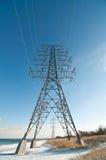 Torre eléctrica (pilón de la electricidad) al lado de un lago Foto de archivo