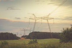 Torre elétrica da transmissão contra o por do sol/torre elétrica da transmissão contra o por do sol toned foto de stock