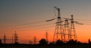 Torre eléctrica de alto voltaje en puesta del sol Foto de archivo libre de regalías