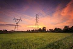 Torre eléctrica de alto voltaje y salida del sol hermosa Fotos de archivo libres de regalías