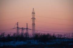 Torre elettrica ad alta tensione della siluetta Fotografia Stock