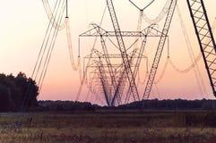 Torre elettrica ad alta tensione della siluetta su tempo di tramonto Immagine Stock Libera da Diritti