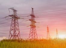 Torre elettrica ad alta tensione della trasmissione al tramonto Immagini Stock