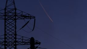 Torre elettrica ad alta tensione, fumo nero dalla fabbrica e traccia dall'aereo su un cielo di sera 4K archivi video