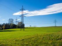 Torre elettrica su un'erba verde del cielo blu del campo fotografia stock