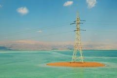 Torre em uma terraplenagem arenosa contra um céu azul com nuvens, uma torre da eletricidade com fios no Mar Morto, foto de stock royalty free